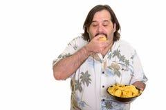 Жирный кавказский человек есть вкусно полный рот обломоков готовых для стоковая фотография