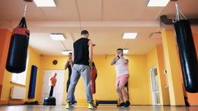 Жирный парень и тонкая женщина с личным тренером в спортзале Дуновения поезда в боксе Здоровье и фитнес Тренировка и практика видеоматериал