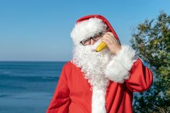 Жирный человек в стеклах одетых как Санта держит банан на океане Каникулы и здоровый образ жизни стоковые фотографии rf