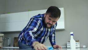 Жирный человек обтирает таблицу с тканью вискозы в кухне Парень очищает поверхность таблицы с чисткой сток-видео