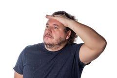 Жирный человек смотря прочь пока держащ его руку над его глазами для того чтобы защитить от лучей солнца стоковые фотографии rf