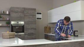 Жирный человек с бородой подготавливая кофе утра и принимая поддерживая глоточек кофе, замедленного движения, современной кухни акции видеоматериалы