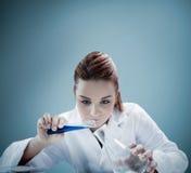 Жидкость белокурого ученого лить в erlenmeyer стоковая фотография