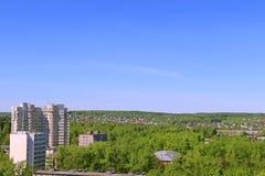 Жилые дома высотного здания среди зеленых деревьев Стоковые Изображения