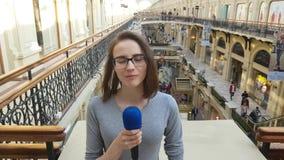 Журналист женщины и вручитель ТВ говорят в микрофон акции видеоматериалы