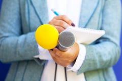 Журналист женщины принимая примечания на пресс-конференцию стоковое изображение rf