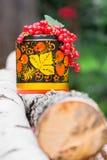 Журналы березы и декоративный деревянный бак в Khokhloma вводят в моду, переполненный пуками зрелой красной смородины Стоковое Изображение