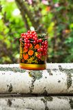Журналы березы и декоративный деревянный бак в Khokhloma вводят в моду, переполненный пуками зрелой красной смородины Стоковые Фото