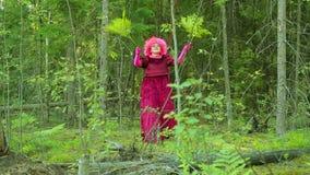 Жуткая ведьма в ритуальных одеждах в лесе выполняет ритуальный танец с ветвями папоротника сток-видео