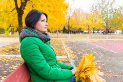Ждать молодой женщины сидя на скамейке в парке Стоковые Фото