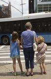 Ждать для того чтобы пересечь женщину оживленной улицы с 2 детьми Стоковые Фотографии RF