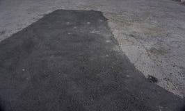 Заасфальтируйте заплату гудронированного шоссе на конкретной земной дороге мостоваой ремонта в месте для стоянки стоковое изображение rf