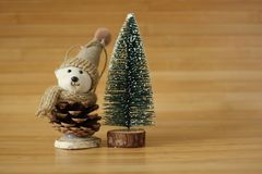Забавляйтесь медведь с шляпой рядом с декоративным деревом chrismas на коричневой предпосылке древесной зелени Стоковое фото RF