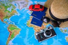 Забавляйтесь автомобиль с пасспортом шляпы и старая камера на карте стоковые фото
