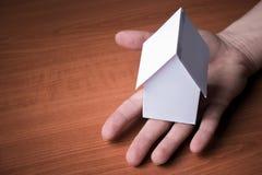Забавляйтесь бумажный дом на человеческой руке, скопируйте предпосылку космоса Стоковая Фотография RF