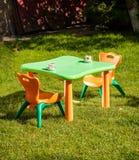 Забавляйтесь пластичные стул и таблица на траве на дворе Стоковые Фотографии RF