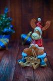 Забавляйтесь северный олень рождества в одеждах рождества сидя на деревянном Стоковые Изображения RF