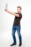Забавляя сконцентрированный молодой человек делая selfie используя таблетку Стоковая Фотография RF