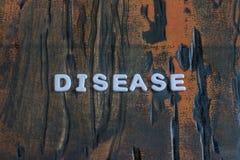 Заболевание слова написанное в белых печатных буквах стоковое фото rf