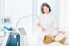 Забота кожи стороны Женщина получая лицевую обработку лазера стоковые изображения rf