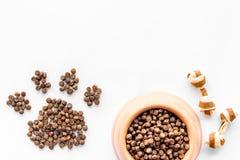 Забота любимчика с сухой едой для собаки в пластичных шаре и лапке на белом космосе взгляд сверху предпосылки для текста Стоковое Изображение