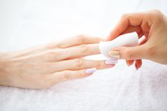 Забота руки и ногтя Красивые руки ` s женщин с совершенным маникюром Мастер маникюра держа пусковые площадки хлопка в руках День  стоковые изображения