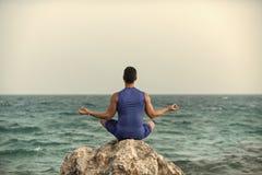 Забота Healt Йога человека практикуя около голубого океана Стоковое фото RF