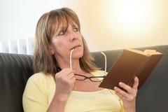 Заботливая женщина держа ее стекла и читая книгу, световой эффект Стоковое фото RF