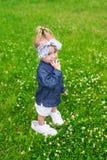 Заботливая маленькая девочка в больших тапках стоя на зеленой лужайке лета Стоковое Изображение RF