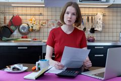 Заботливое усиленное молодое женское усаживание на кухонном столе при бумаги и портативный компьютер пробуя работать через кучу с Стоковое Фото