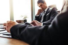 Заботливый бизнесмен сидя на его столе с партнером стоковое фото rf