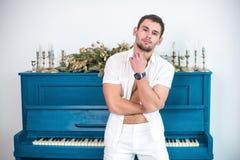 Заботливый, красивый человек с бородой в белых одеждах на фоне рояля, rasped рубашки с чуть-чуть торсом Стоковое фото RF