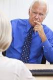 Заботливый старший бизнесмен в офисе на столе Стоковые Фотографии RF