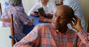 Заботливый старший человек сидя в кресло-коляске пока старшие друзья взаимодействуя в предпосылке 4k акции видеоматериалы