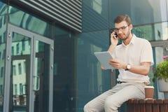 Заботливый multitasking бизнесмена outdoors Стоковые Изображения