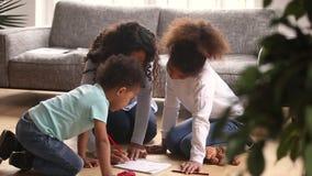 Заботя африканский чертеж матери с покрашенными карандашами играя с детьми сток-видео
