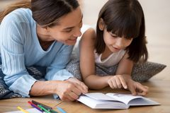 Заботя мама читая интересную книгу с небольшой дочерью стоковая фотография