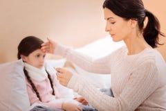 Заботя мать измеряя температуру ее ребенка Стоковое Изображение RF