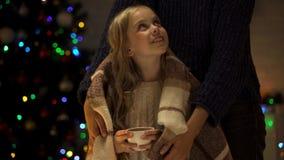 Заботя мать покрывая милую чашку удерживания девушки какао с шотландкой, временем рождества стоковое изображение