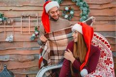 Заботя парень покрывает его девушку с теплым blanke indoors стоковые изображения