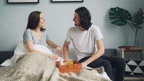 Заботя парень принося завтрак для того чтобы положить в постель для говорить жены спать целуя дома видеоматериал