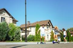 Заботя порция человека и дочери будет матерью hoverboard катания Стоковая Фотография RF