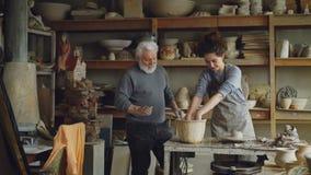 Заботя старший дед показывающ молодому granddoughter как работать с глиной на бросать-колесе в мастерской гончарня акции видеоматериалы