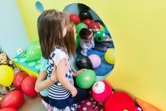 Заботя учитель направляя застенчивую девушку пре-школы во время playtime стоковые фото