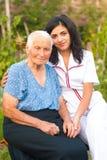 Заботя доктор с больной пожилой женщиной outdoors Стоковые Фотографии RF