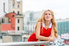 Заботливая блондинка в красном платье на балконе в городе Стоковые Фотографии RF
