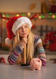 Заботливая девушка в шляпе santa с молотком и копилкой Стоковое фото RF