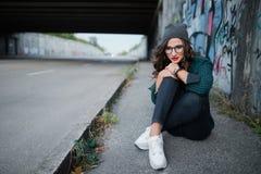 Заботливая девушка сидя на пустом шоссе под мостом и думает Стоковые Изображения RF