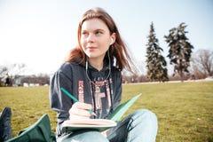 Заботливая женщина в наушниках сидя и писать в тетради outdoors Стоковые Фото