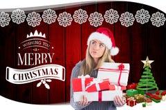 Заботливая женщина в шляпе santa держа подарки рождества Стоковая Фотография